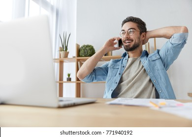 Positive carefree bearded male freelancer wears spectacles and denim shirt pleased to hear friend via smart phone, has break after work on laptop computer, shares his success and achievement.