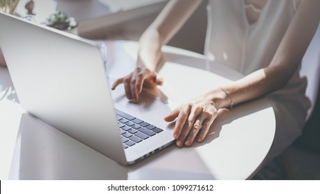 Positive casual beautiful woman working on a laptop sitting at the table in living room of modern house.