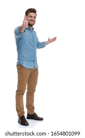 Positive casual man gesturing ok, presenting and smiling while standing on white studio background
