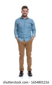 Positive casual man laughing with both hands in his pockets while standing on white studio background