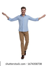 Positive casual man smiling and inviting while wearing shirt and walking on white studio background