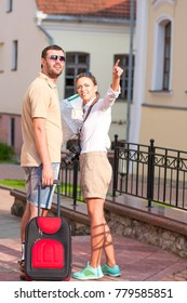 Positive Caucasian Couple Traveling with Trolley Suitcase Outdoors. Checking Route Using City Map. Posing with Photocamera.Vertical Image