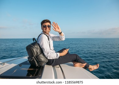Positive caucasian freelancer with backpack over his shoulder spending resttime at sea journey, smiling at camera, enjoys sunset from yacht.
