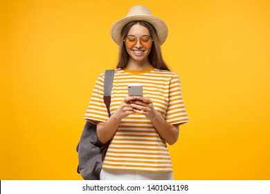 Positive Caucasian girl isolated on yellow background browsing pages in her smartphone ready to travel