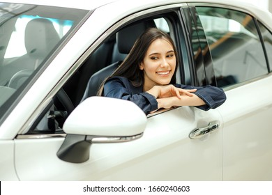 positive caucasian lady sitting inside of her new car in dealership. young beautiful woman happy after buying representative car
