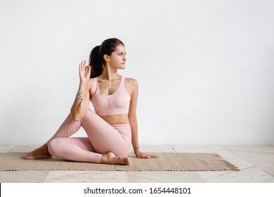 Positive kaukasische junge Brunette Frau, die Halbfürst der Fische Übung, Ardha Matsyendrasana posieren Yoga tun. Yogalehrerin, die Gomukhasana auf weißem Hintergrund macht. Werbefläche