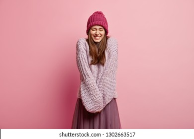 Positive Caucasian young female model keeps hands together, wears long sleeved knitted sweater, pink hat, closes eyes from pleasure, models over rosy background. People and emotions concept.