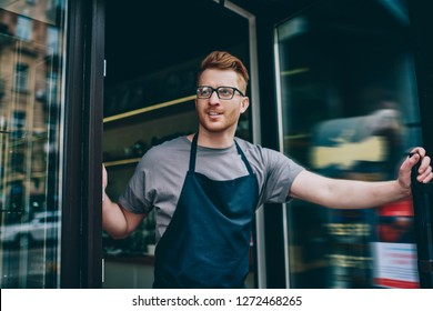 Positive caucasian young man in apron working waitress in cafeteria opening entrance door and inviting guests on tasty coffee developing own business.Cheerful owner of cafe working barista