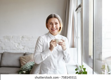 Positive cheerful 60 year old woman medical expert with gathered hair standing by large window in modern apartment interior, having coffee break while working from home, consulting patients