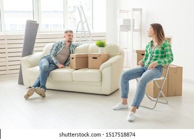 Positive cheerful couple rejoices in moving their new apartment sitting in the living room with their belongings. Concept of housewarming and mortgages for a young family.