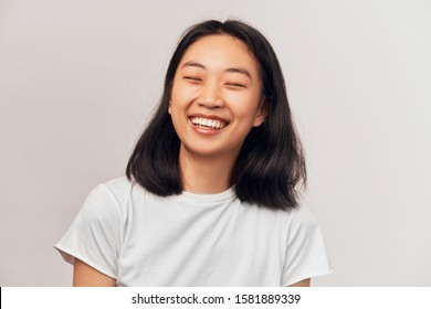 Positive cheerful female closing eyes tight cannot stop laughing at good joke. Beautiful young woman of Asian appearance with black hair brown eyes wearing t-shirt stands on white background in Studio