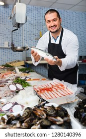 Positive cheerful friendly seller behind scales and fish counter showing fish in his hands
