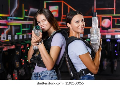 Positive cheerful glad girl took aim and holding guns during laser tag game in dark labyrinth indoor