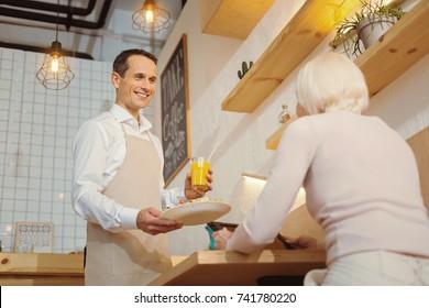 Positive cheerful man looking at his customer