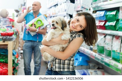 Positive cheerful smiling female with dog in pet shop, during shopping with man