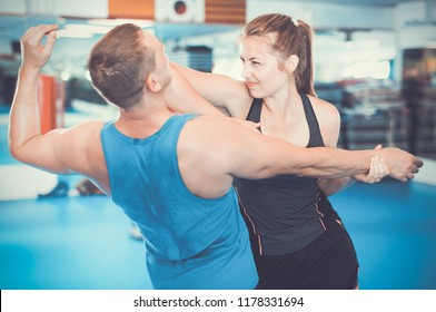 Positive cheerful  woman is training with man on the self-defense course in gym.