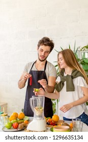 positive cheerful young fashion people are adding berries and kiwi to a juicer. creative beverage