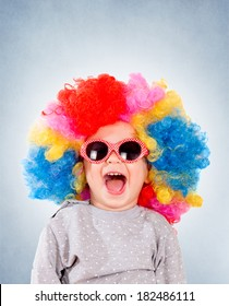 Positive child with sunglasses and clown wig isolated on blue background