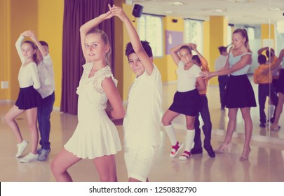 Positive children  enjoying of partner dance in class