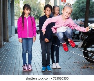 Positive children play on city sidewalk in autumn city