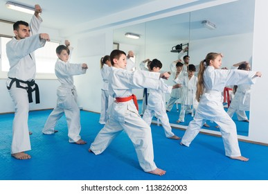 Positive children trying a new moves with coach during karate class