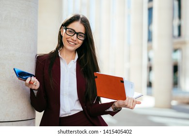 Positive clever cute charming attractive elegant woman in glasses holding diary, smartphone and pencil. Broad smiling outdoors. Business people concept.