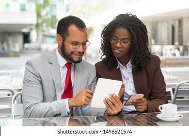 Positive colleagues comparing data on their gadgets screen. Business man and woman sitting in coffee shop, showing tablet and smartphone screens to each other. Comparing data concept