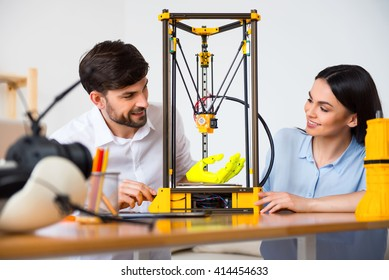 Positive colleagues using 3d printer.