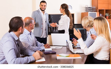 Positive colleagues at working meeting in office with diagram at background