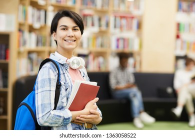 Positive confident female university student with white headphones on neck wearing blue satchel standing in library and holding books while looking at camera