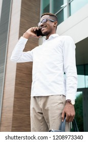 Positive confident handsome young African man in glasses wearing white shirt and expensive watch standing at office building and calling business partner on mobile hone