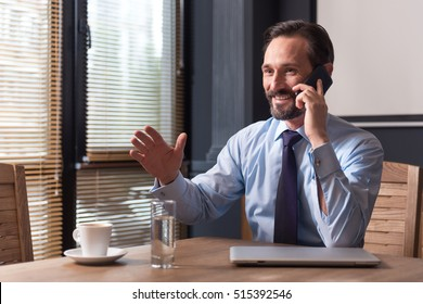 Positive confident man having a conversation on the phone
