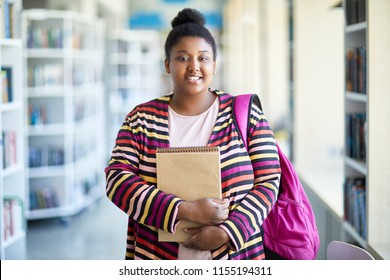 Positive confident overweight African-American student girl in colorful cardigan holding sketchpad and smiling at camera in library