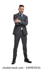positive and confident young business man standing with hands crossed, isolated on white background, full body portrait