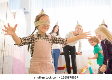 Positive content blindfolded girl in party hat keeping arms outstretched while catching up friends during blind mans buff gamer, she finding other players