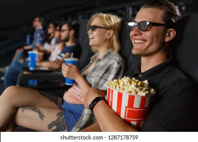 Positive couple in 3d glasses sitting together and smiling at cinema hall. Blonde girlfriend at background and handsome boyfriend eating popcorn and enjoying funny comedy.