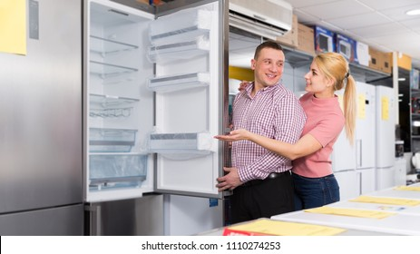 Positive couple chooses refrigerator in shop of household appliances