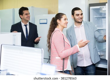 positive couple choosing new refrigerator in hypermarket and smiling