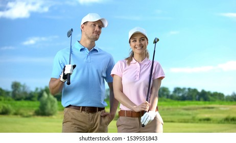 Positive couple of golfers holding clubs looking at course, sport game, career