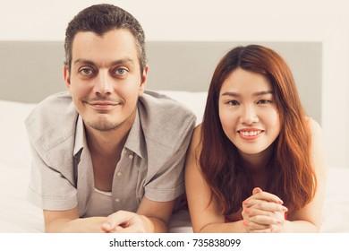 Positive couple lying on soft duvet in bedroom
