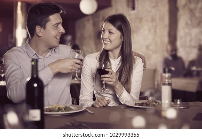 positive couple on romantic date drinking red wine at restaurant