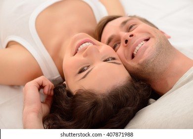 Positive couple relaxing in bed