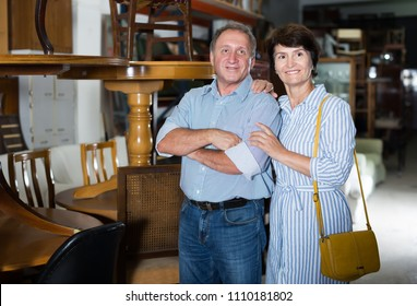 Positive couple is shopping the old table in the antique store