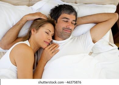 Positive couple sleeping lying in bed