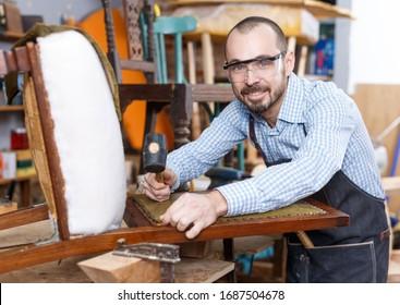 Positive craftsman engaged in repair of vintage furniture, reupholstering chair in workshop