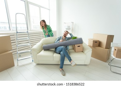 Positive crazy cheerful couple rejoices in moving their new apartment sitting in the living room with their belongings. Concept of housewarming and mortgages for a young family.