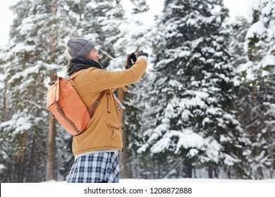 Positive curious young man in winter coat wearing satchel using smarphone while photographing nature during hiking, travel blogger concept