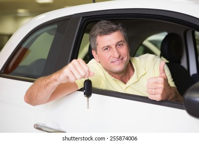 Positive customer holding a key sitting in his car at new car showroom