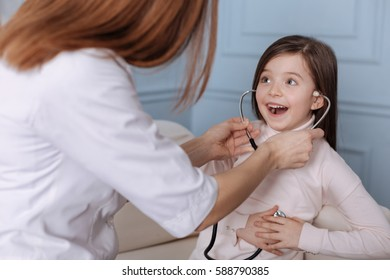 Positive cute little girl playing with stethoscope