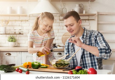 Positive dad and little daughter cooking in kitchen at home. Man teaching girl to add right quantity of salad dressing, copy space
